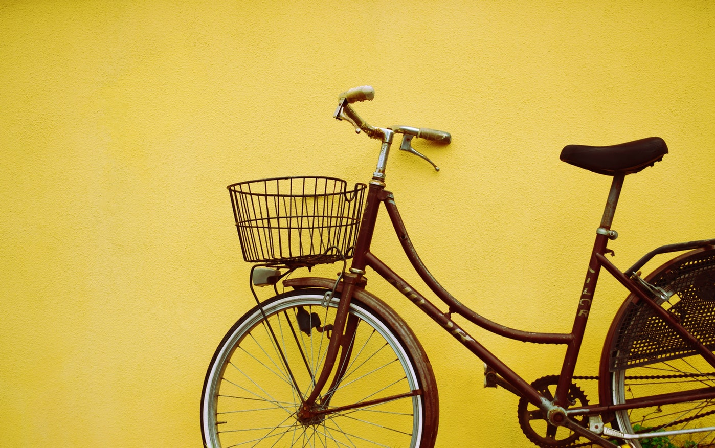 A bicycle against a yellow wall. Cycling is one of the exercises to help with arthritis