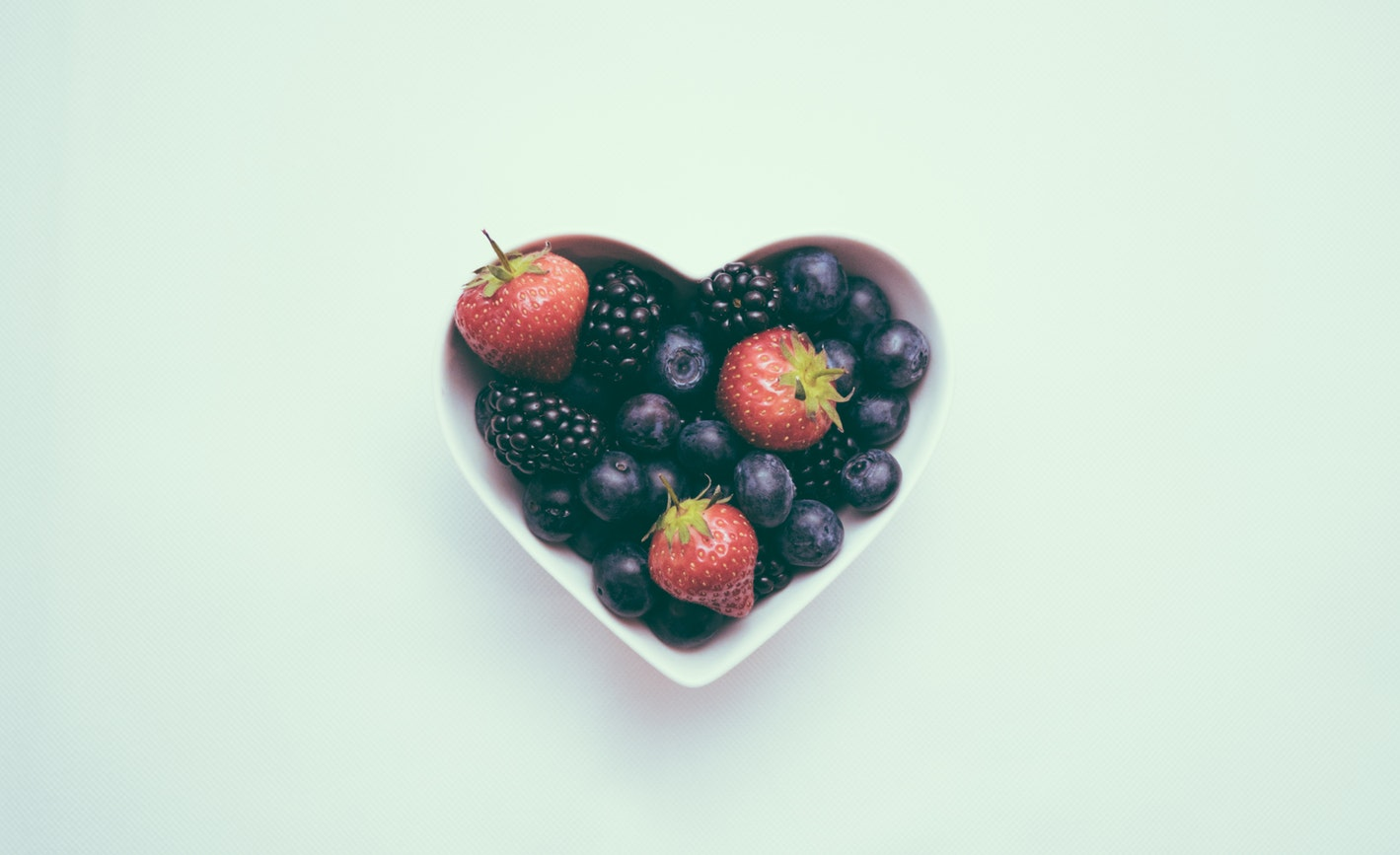 A bowl of fruit in the shape of a heart. Heart disease is one of the 10 common senior health issues.