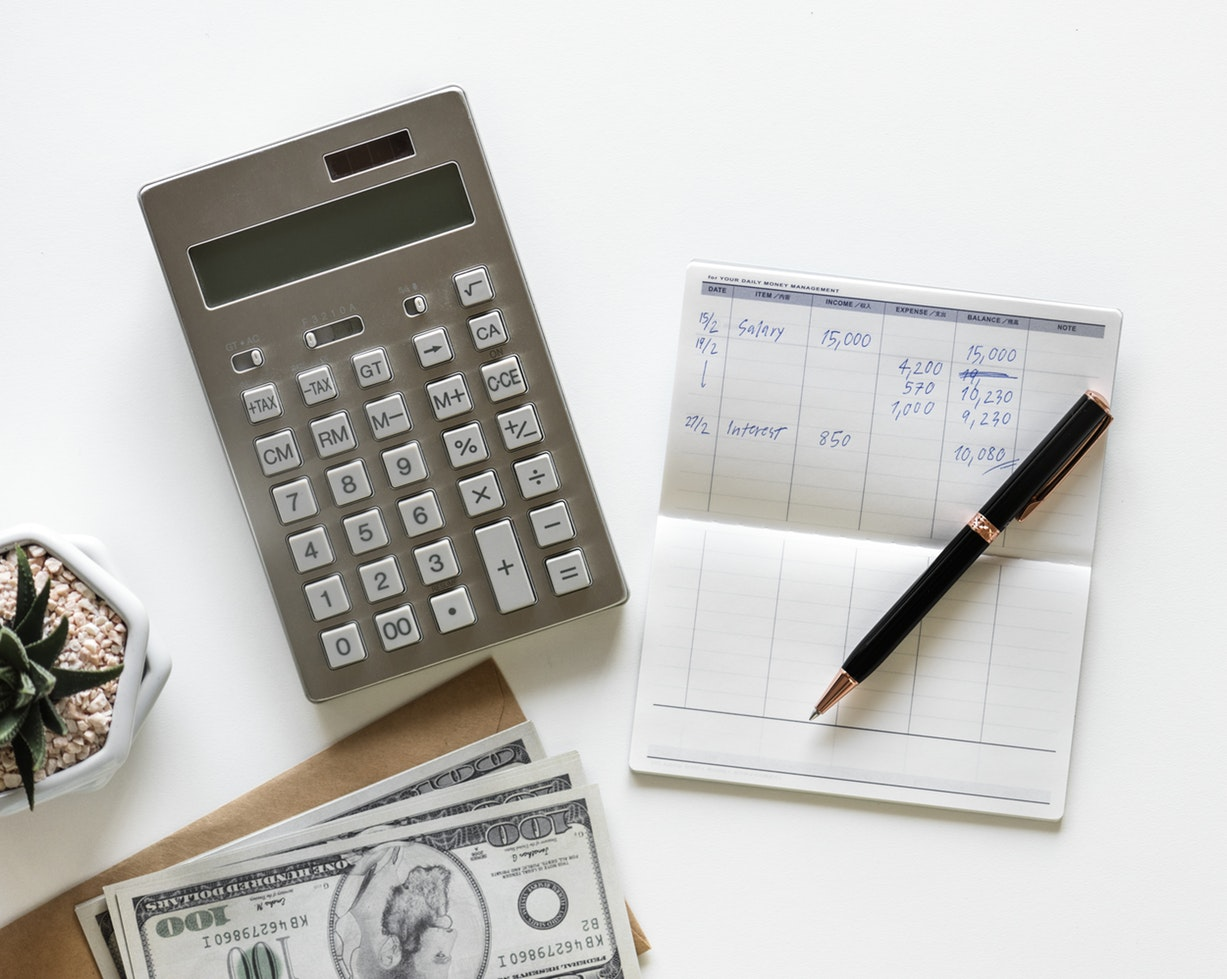 A calculator next to a check book and money