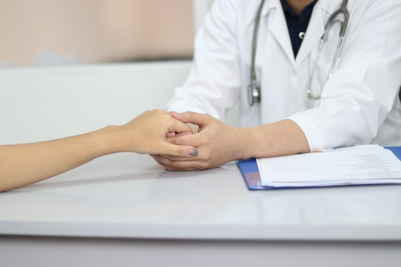 A caregiver holding hands with a doctor that they are talking to.