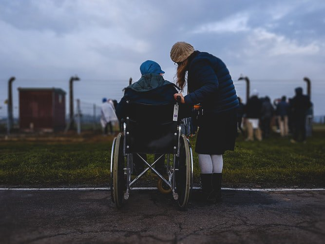 A caregiver with a resident at an assisted living facility watching the sunset outside