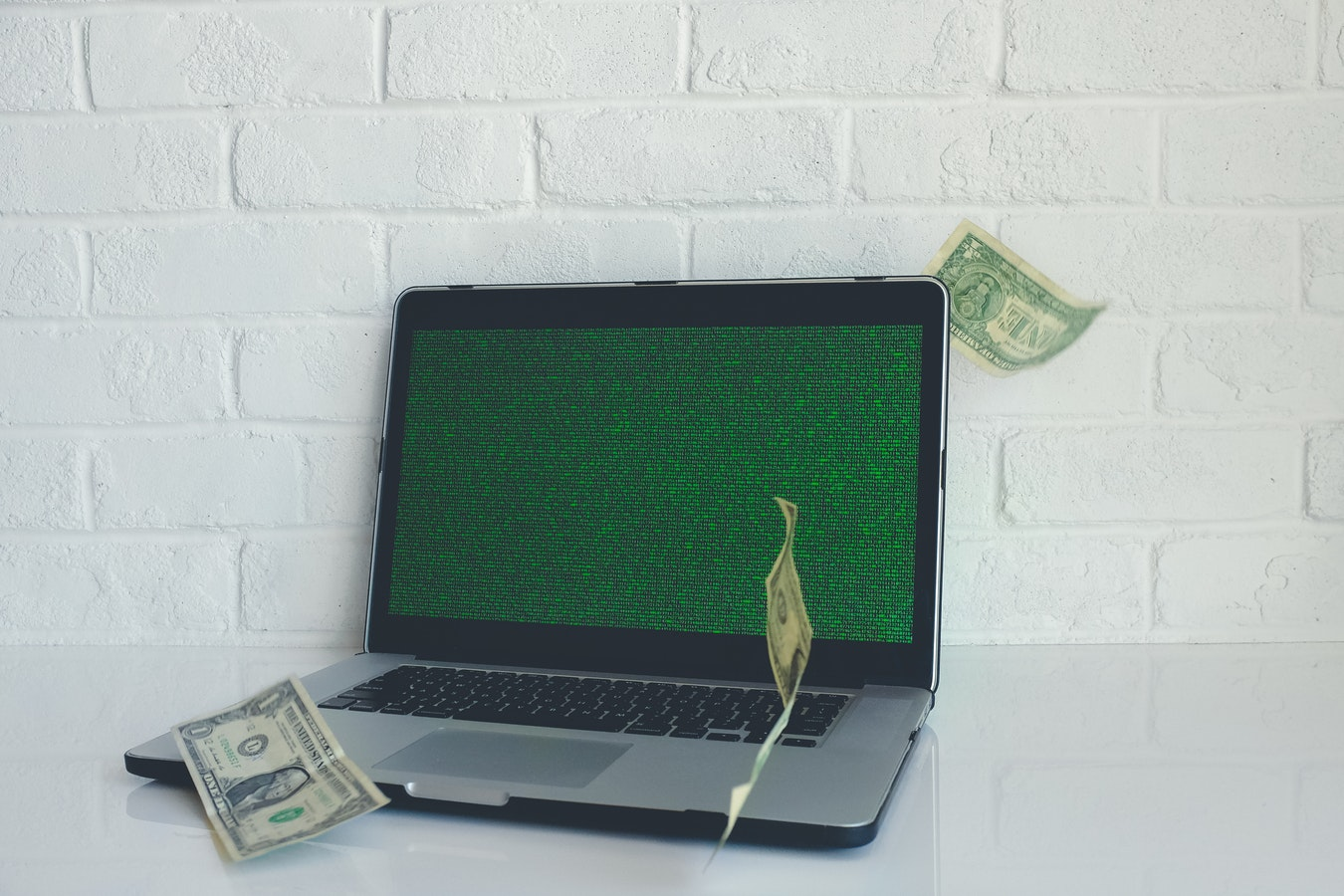 A computer with dollar bills in front of it. Many individuals whose identity is stolen is taken for money
