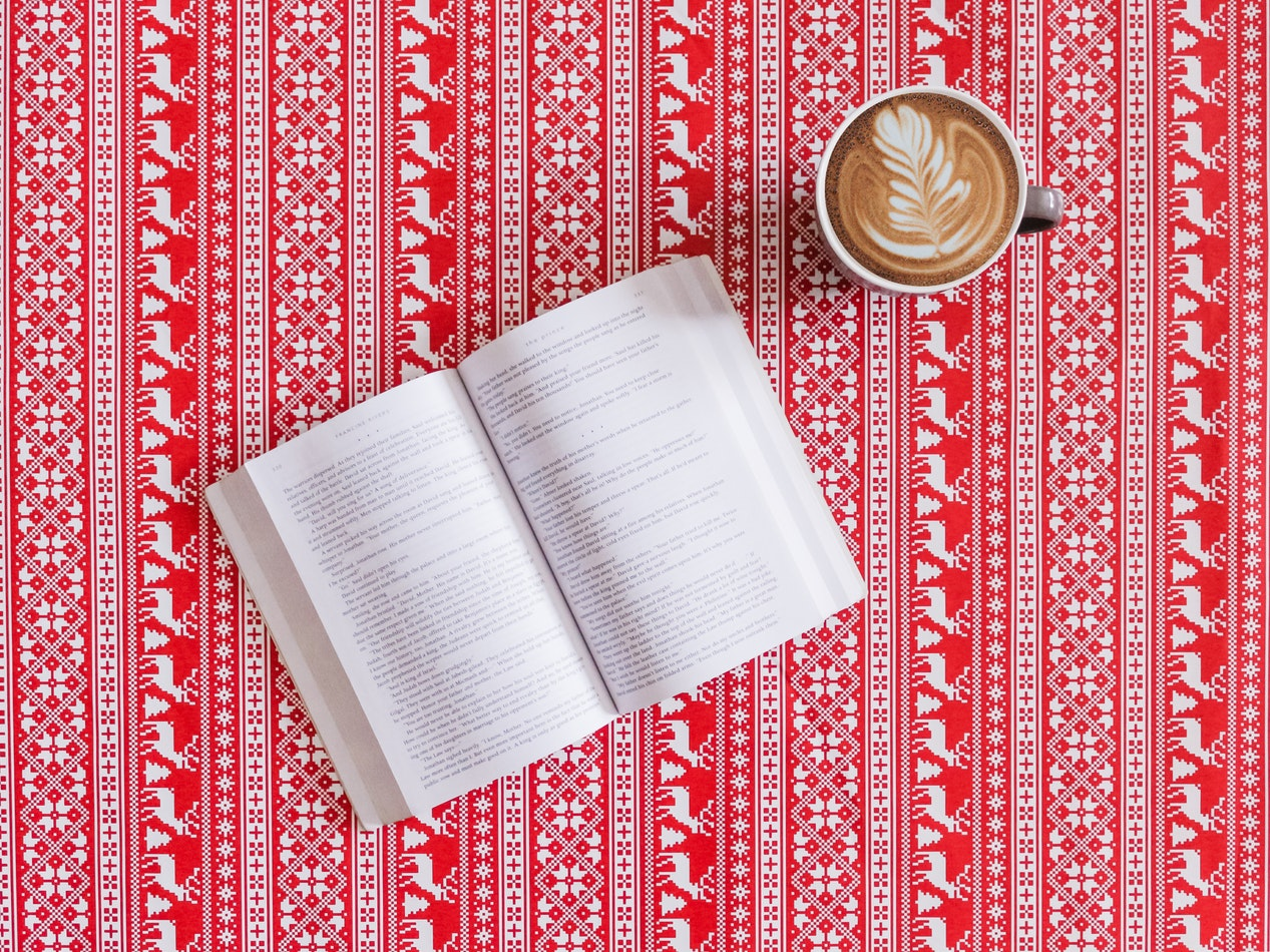 A cup of coffee next to an open book. Reading a book is a great way to keep the mind busy while maintaining cognitive function