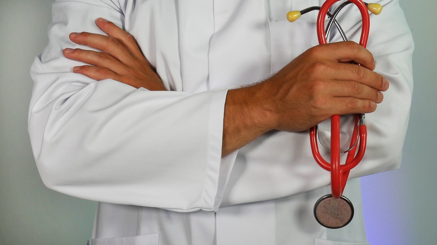 A doctor holding a stethoscope with his arms crossed.