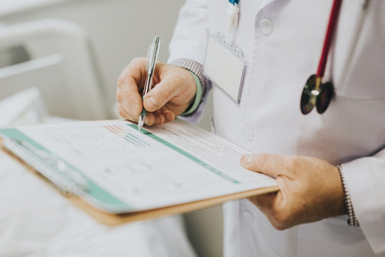 A doctor writing down notes about an individuals parkinson disease stages and treatment.