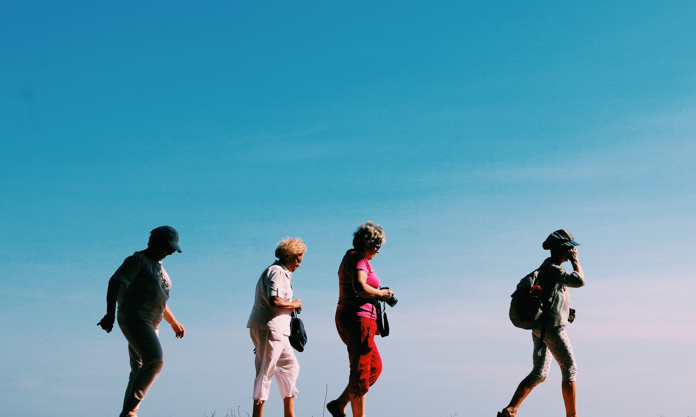A group of elderly women hiking. The benefits of the outdoors for seniors are very high.