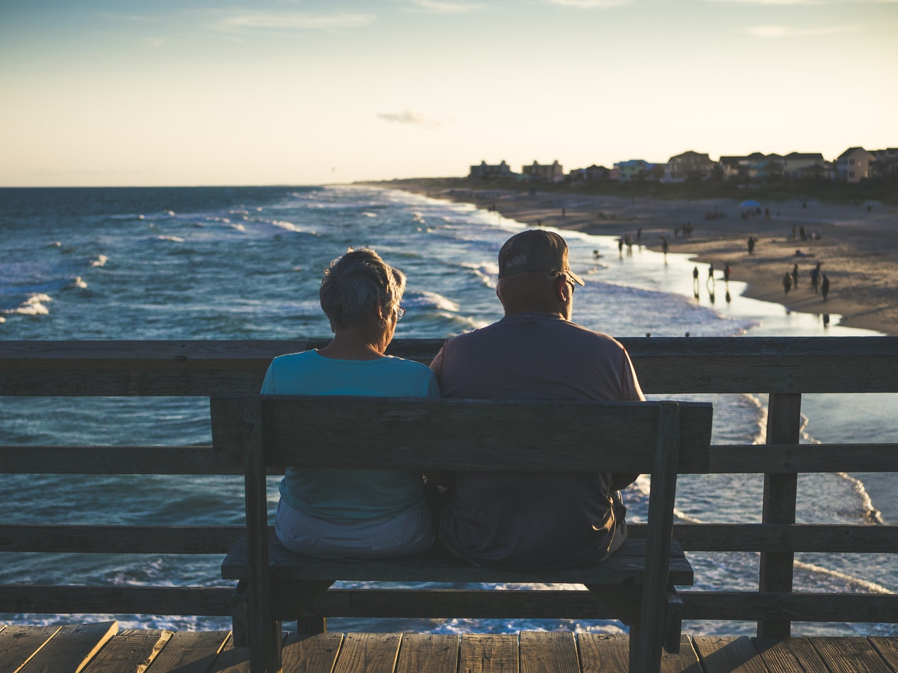 A man and a woman sitting together on a bench looking over the ocean