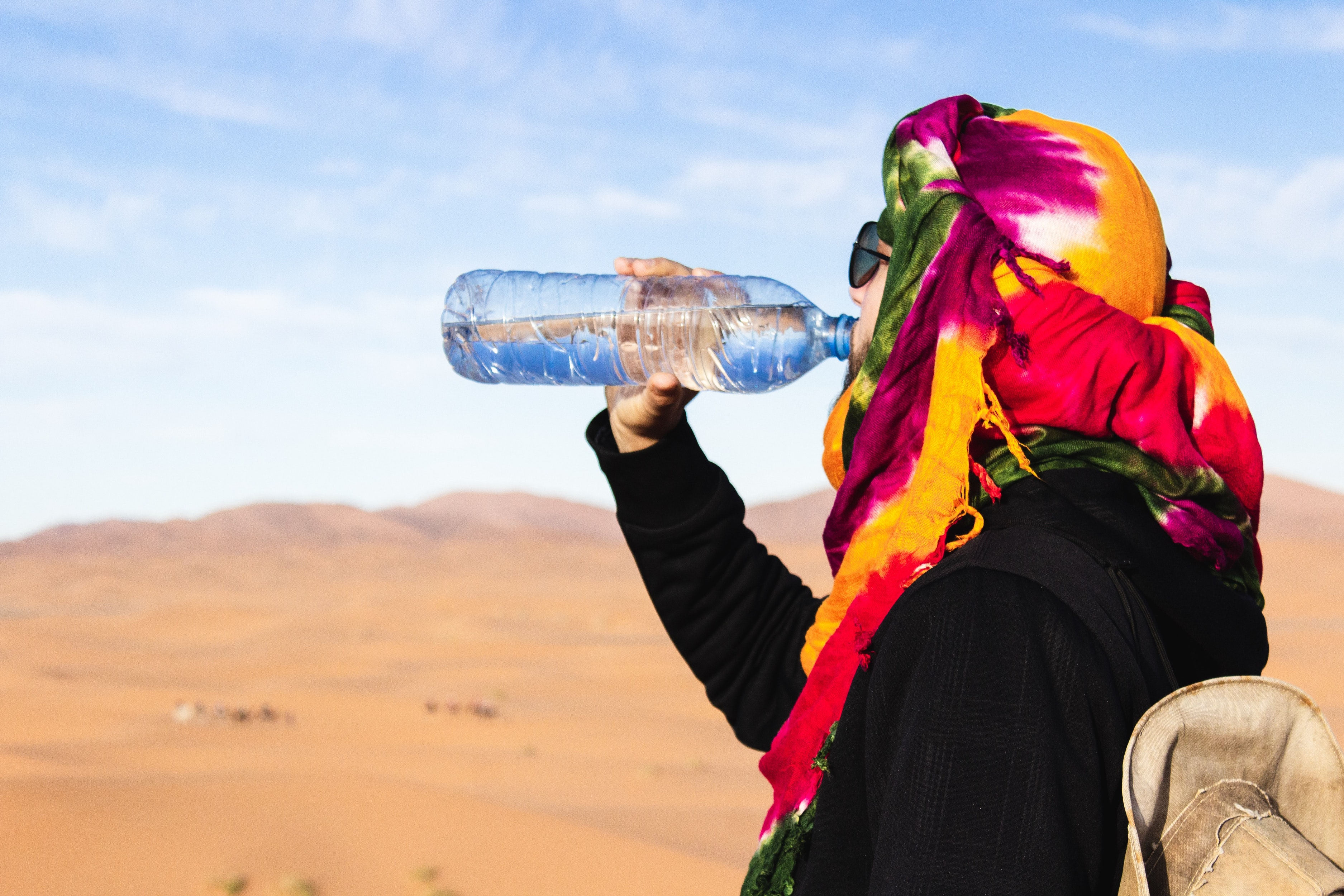 A man in the middle of the desert drinking water. It is important that we are staying hydrated.