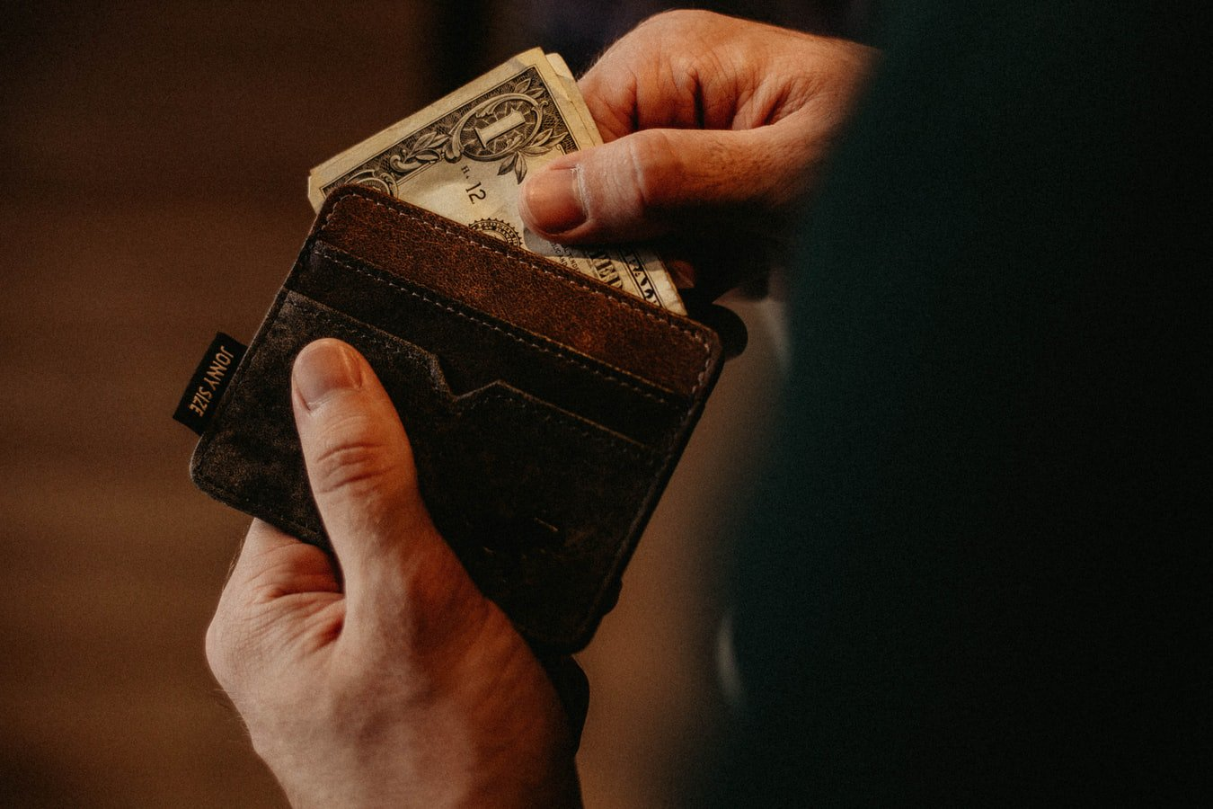A man opening his wallet to pull out money to pay for a senior community
