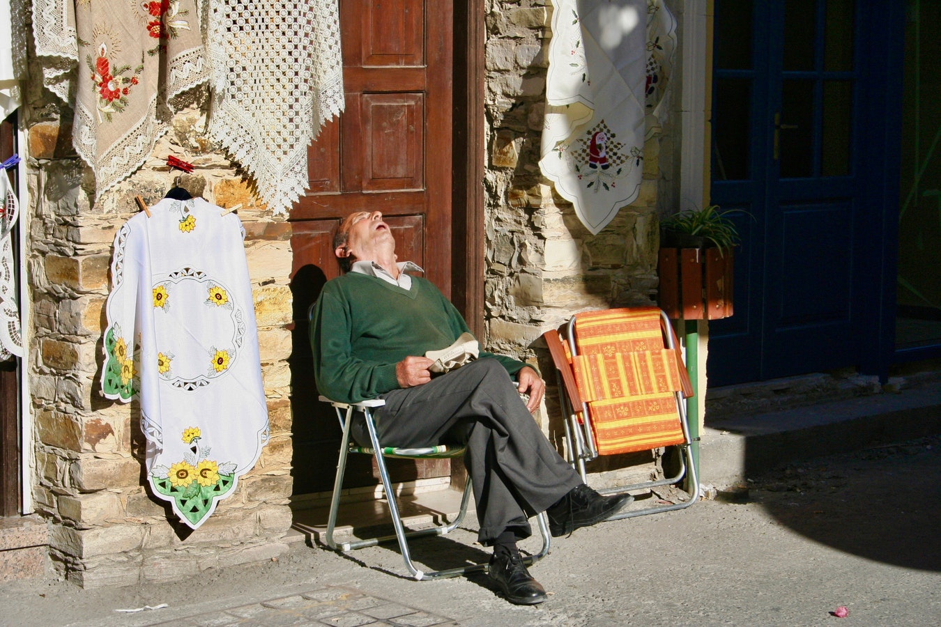 A man sleeping in a chair on the street. Sleep apnea can cause excessive fatigue.