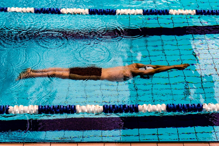A man swimming in a pool as a form of aquatic therapy