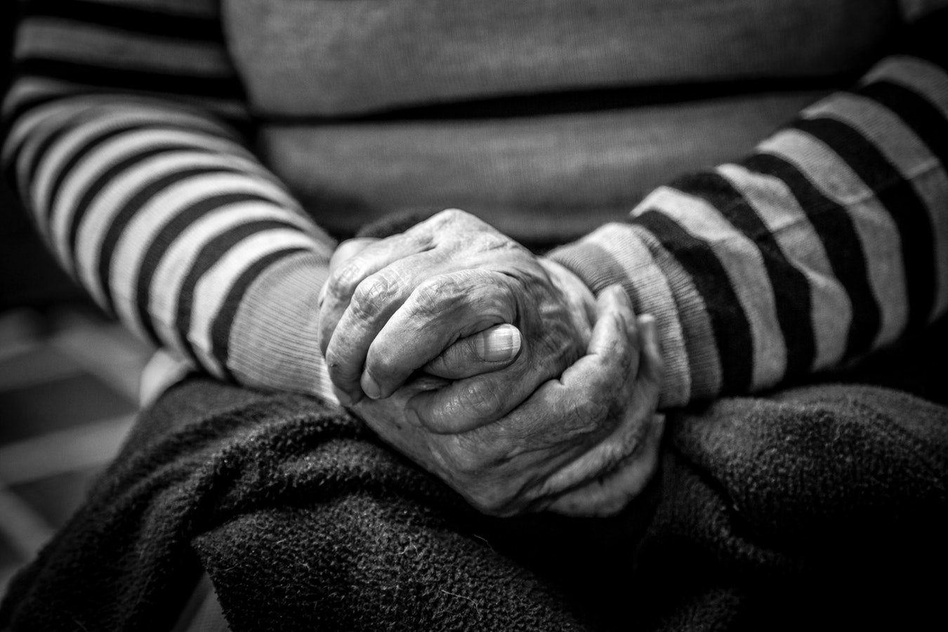 A older woman holder her hands in her lap