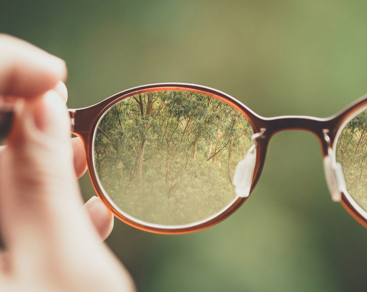 A pair of glasses held by an individual. If youre wondering when it is time to quit driving you might want to go to your doctor for an eyesight and hearing exam.