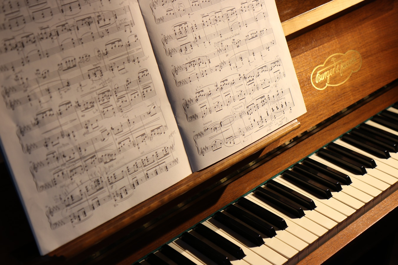 A piano with a music book open so an individual can play songs about growing older
