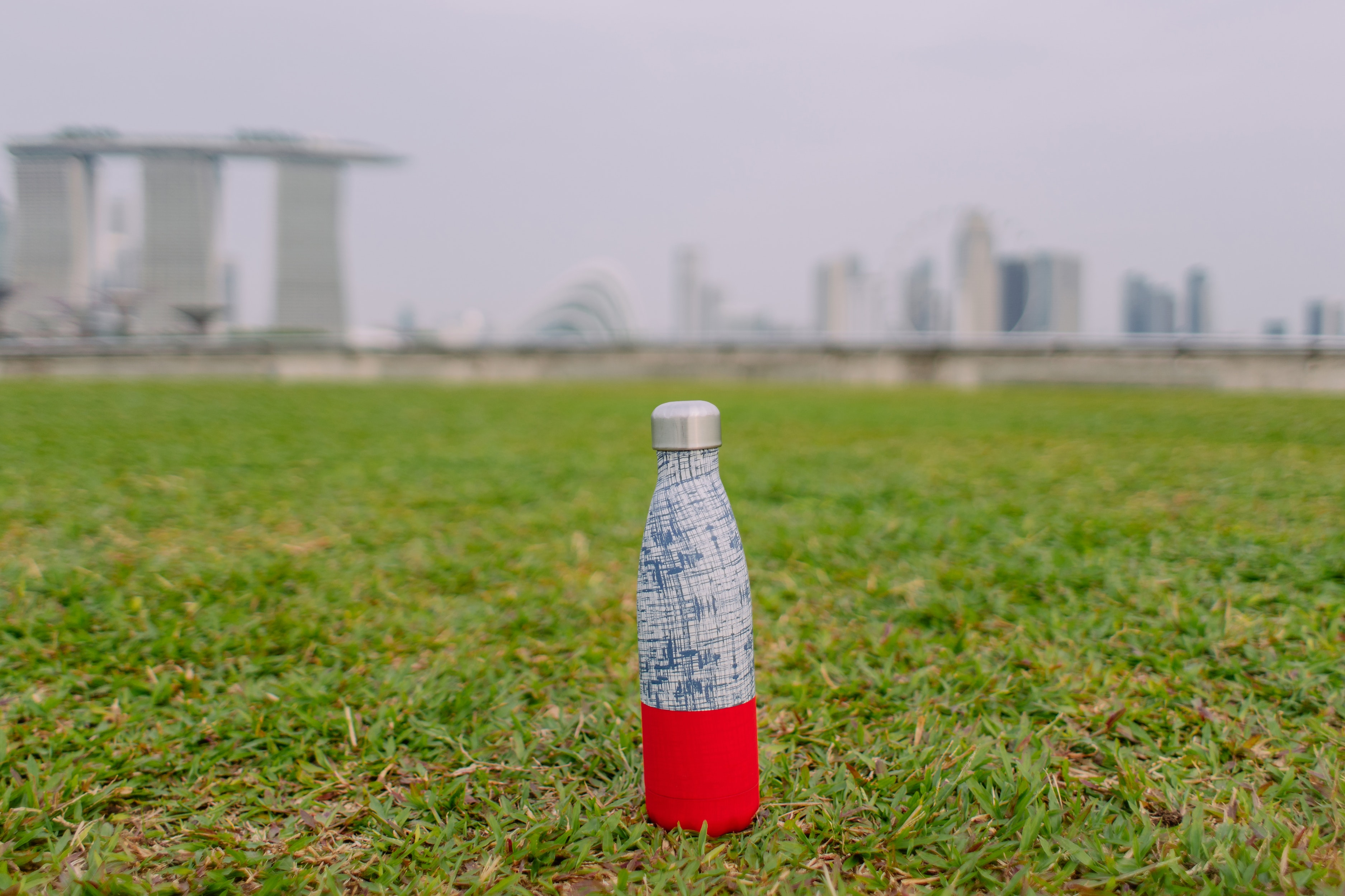 A reusable water bottle in the grass. Staying hydrated is important for our bodies and health as we age.
