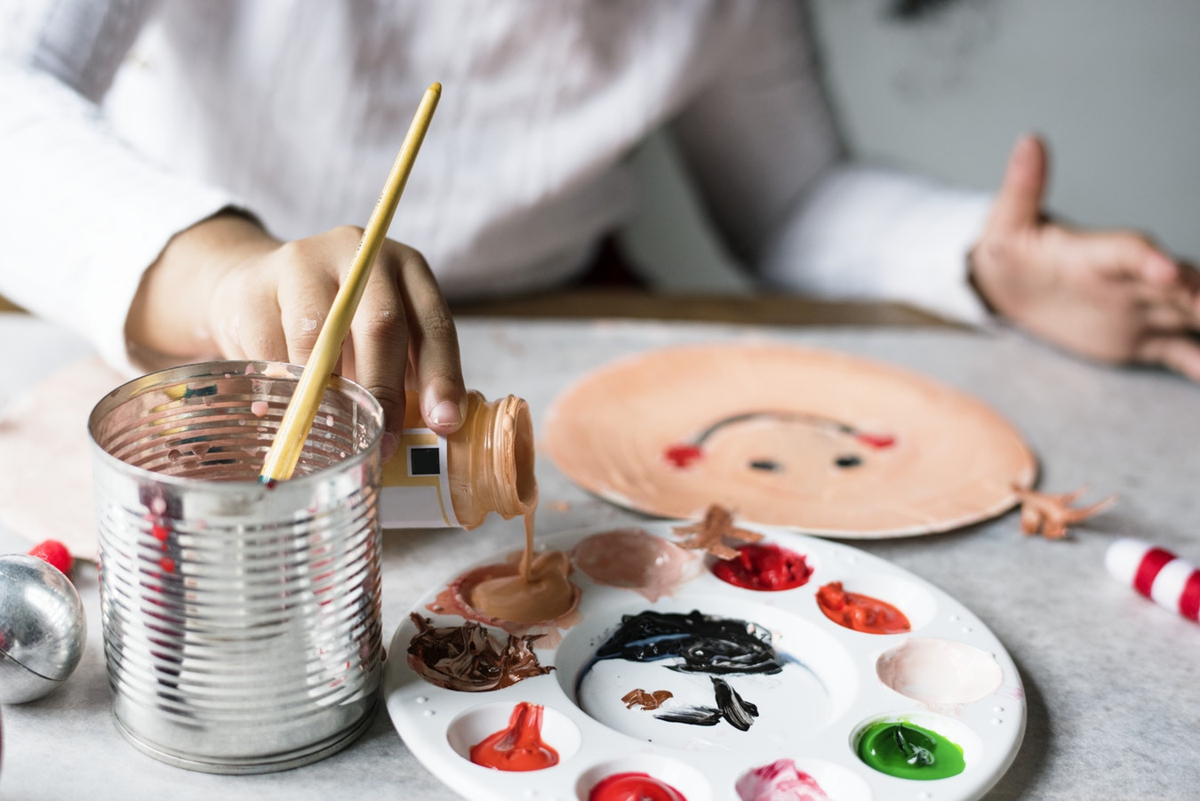 A senior in an assisted living facility painting as a form of expressive art therapy.