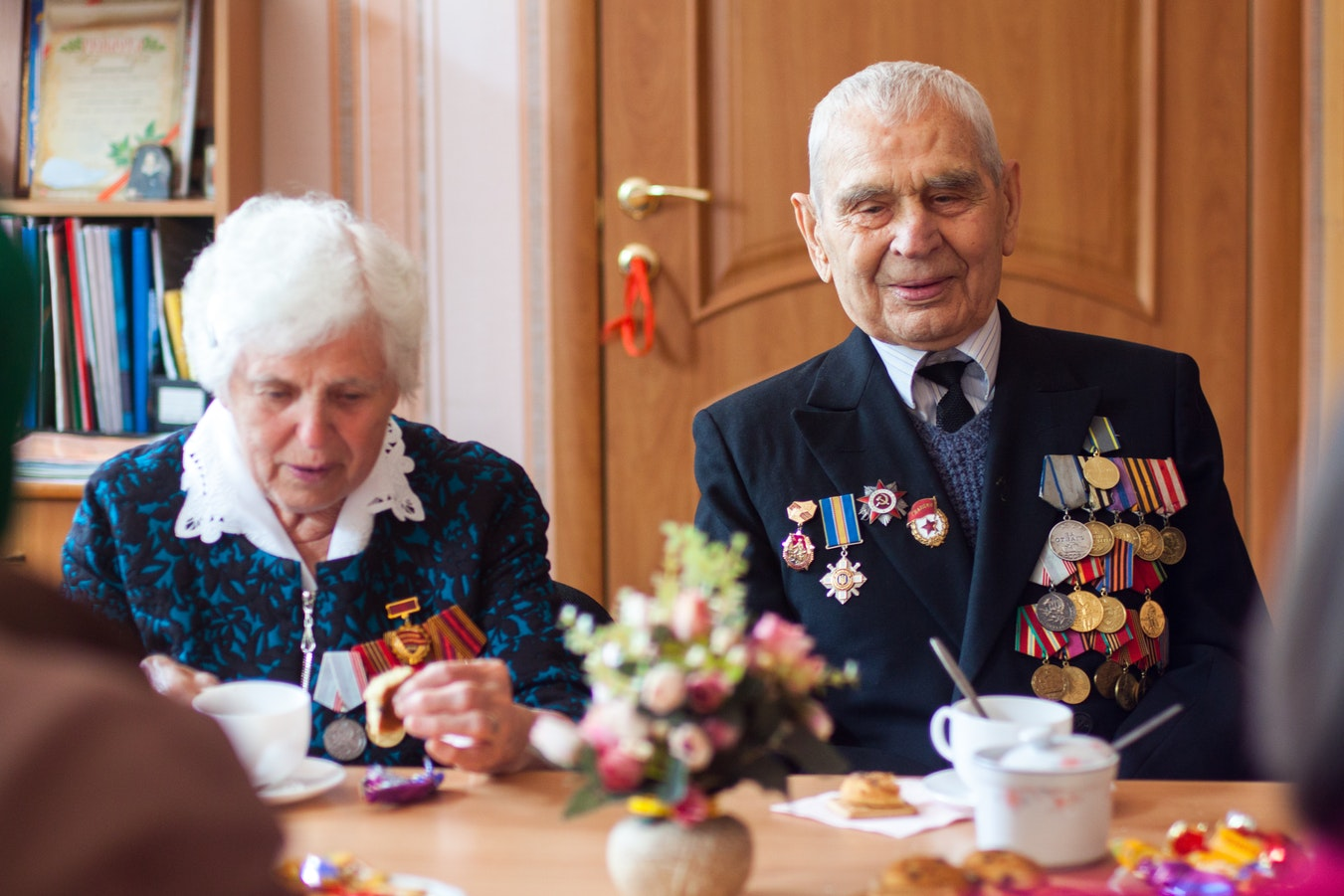A senior veteran and his wife enjoying coffee and cookies at their senior living facility.