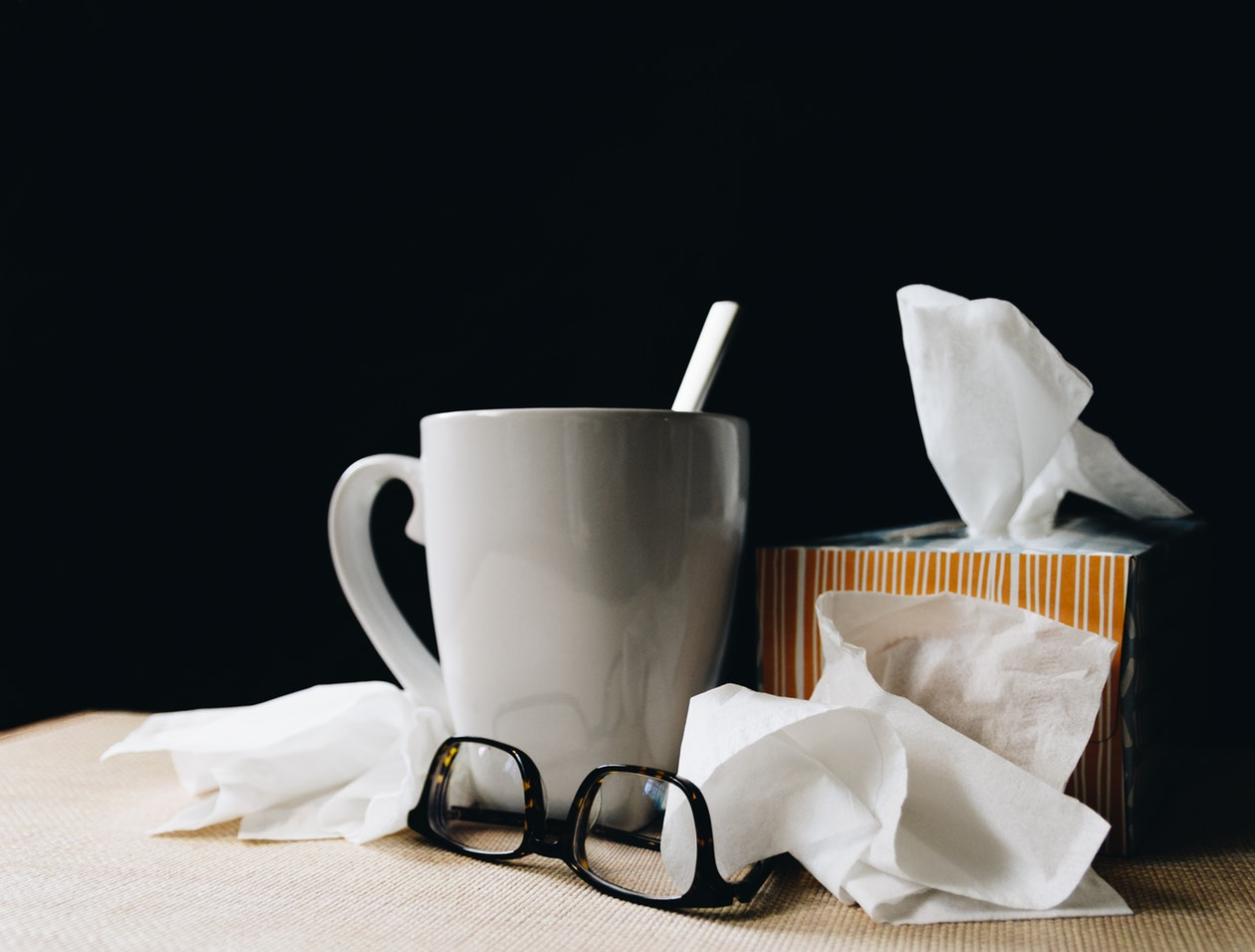 A tissue box, glasses, and a cup of warm tea