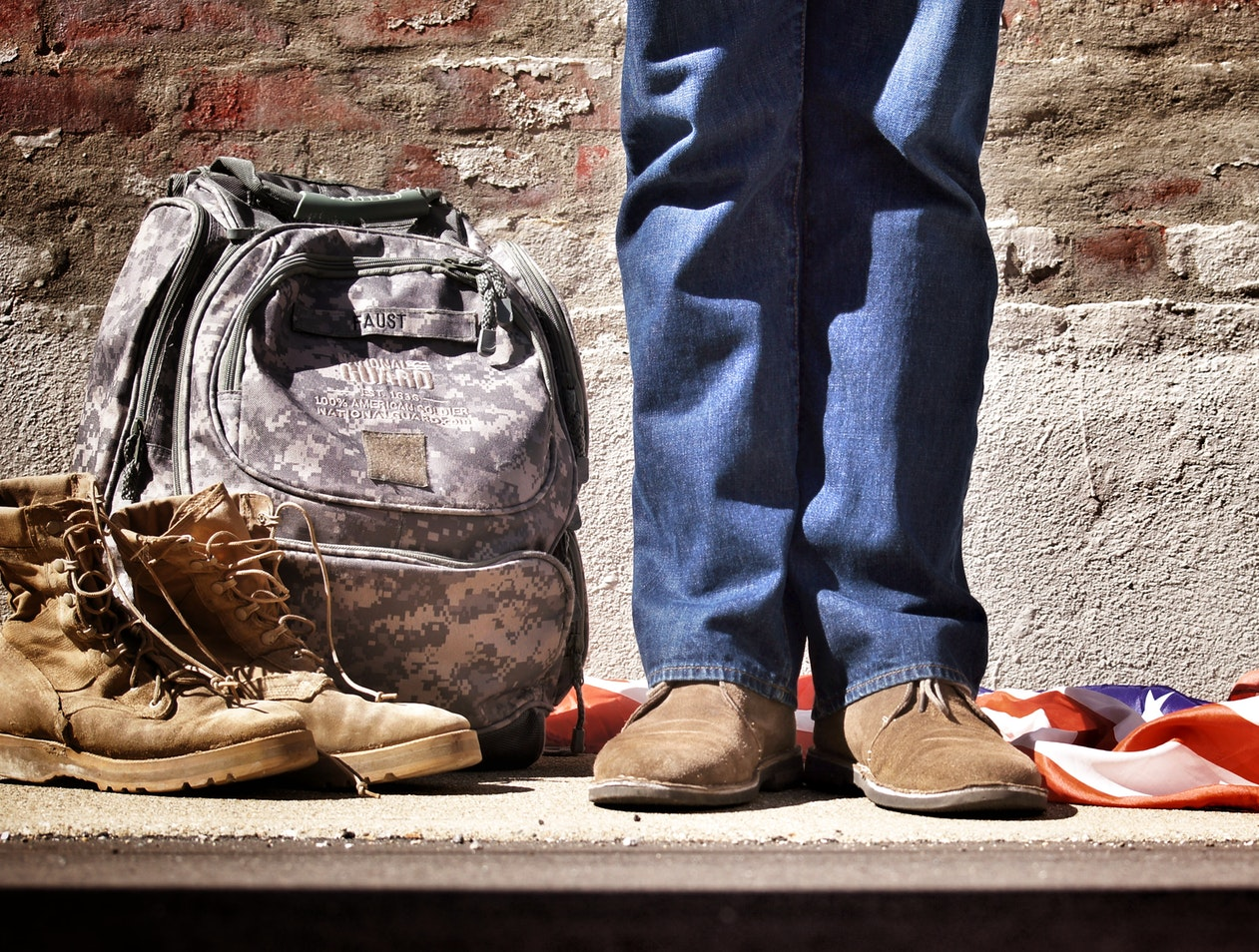 A veteran with his boots and backpack on the floor