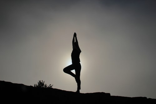 A woman practicing yoga on the moutains. The benefits of the outdoors for seniors are are very high.