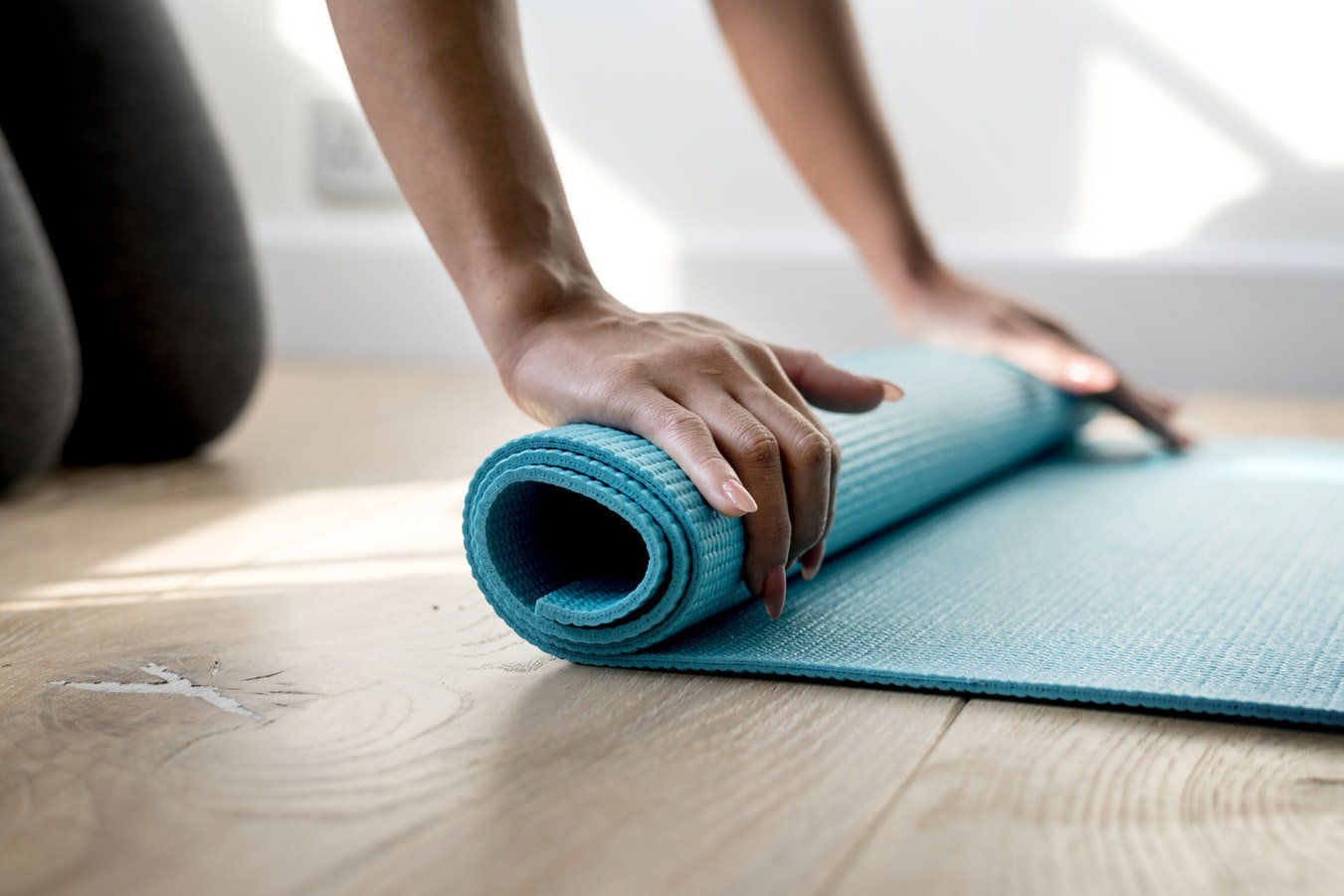 A woman rolling up a yoga mat used for exercise and maintaining cognitive health.
