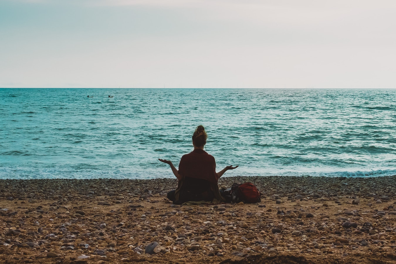 A woman sitting on the beach practicing meditation and breathing techniques