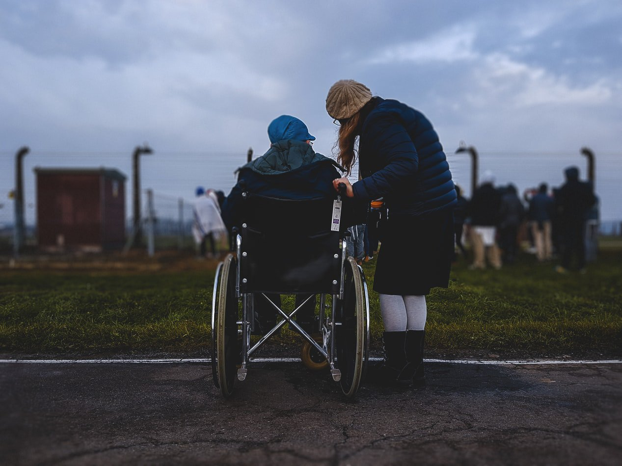 A woman standing next to her mother in a wheelchair who has alzheimers disease.