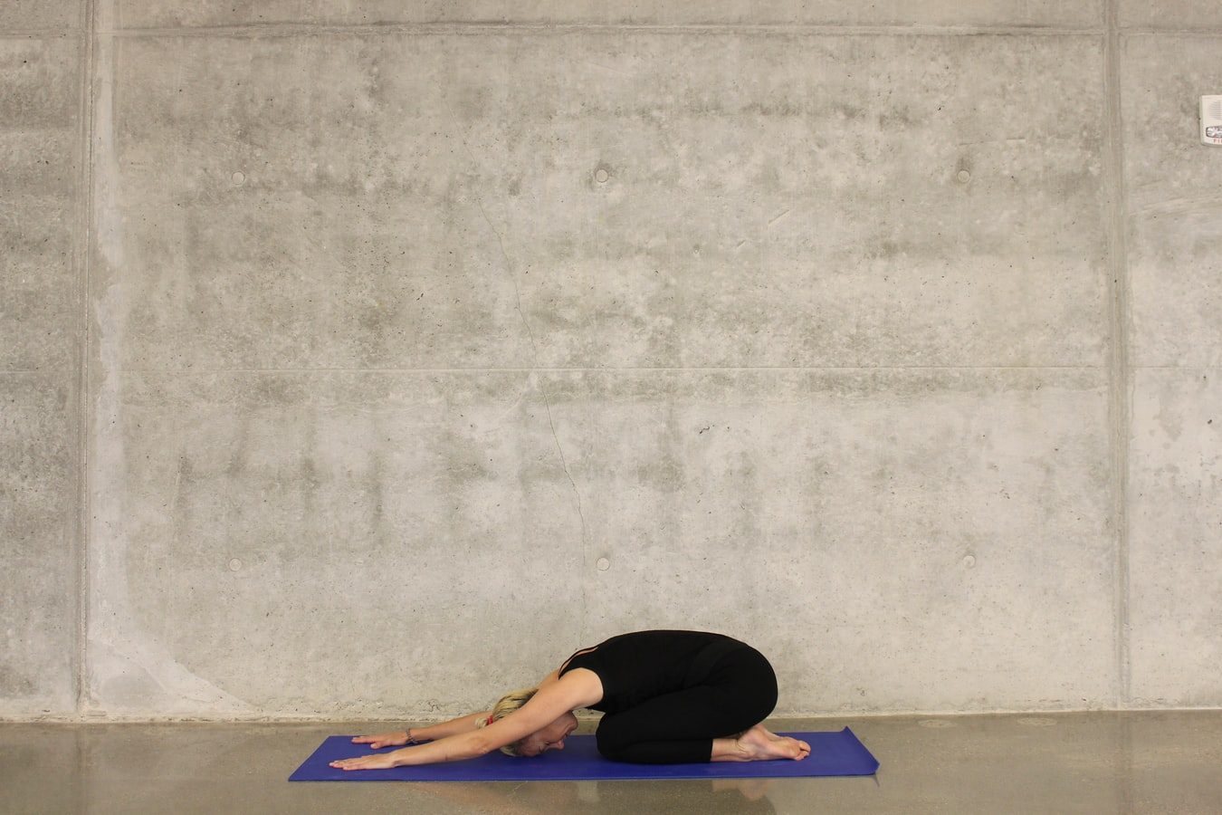 A woman stretching on a yoga man. Stretching is a great way to help seniors stay active