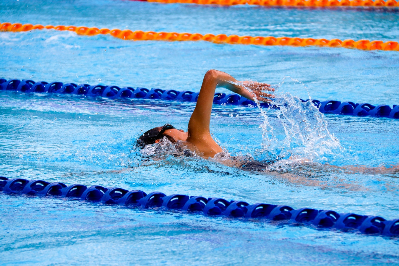 A woman swimming laps in the pool. The benefits of the outdoors for seniors are very high.