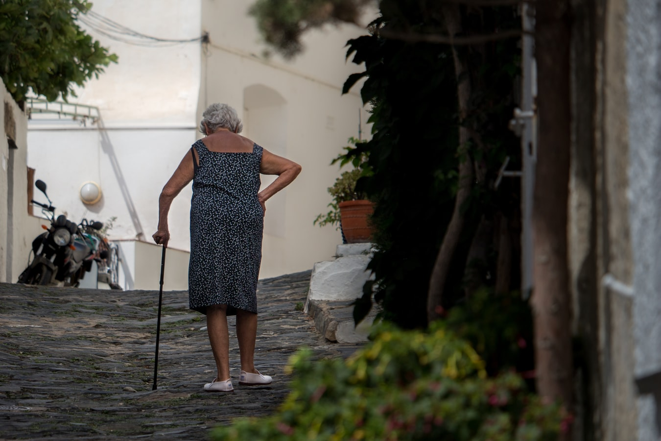 A woman walking up the street with a cane. There are many ways one can help with preventing senior falls