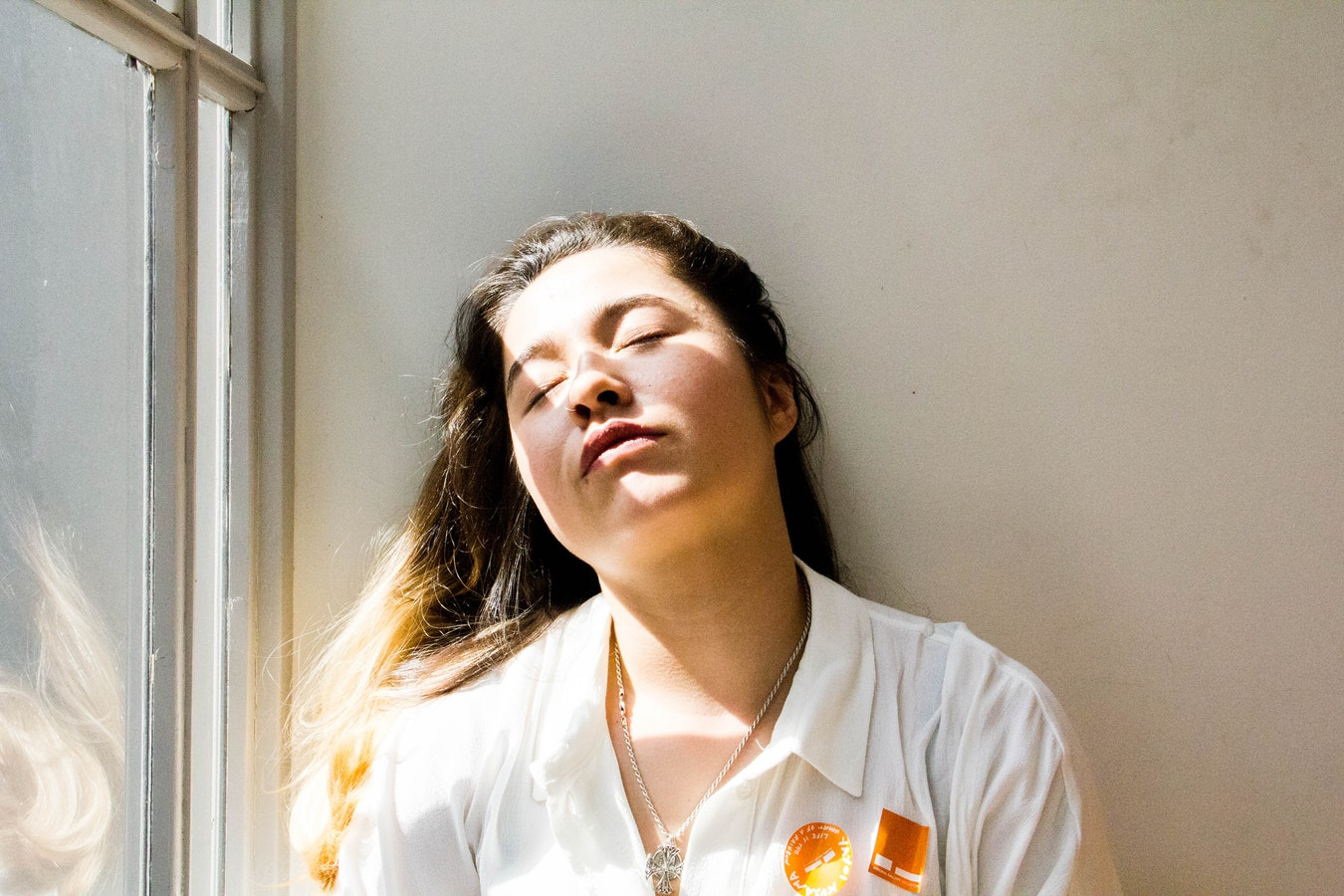 A woman who is tired and laying up next to a wall because she is experiencing caregiver fatigue