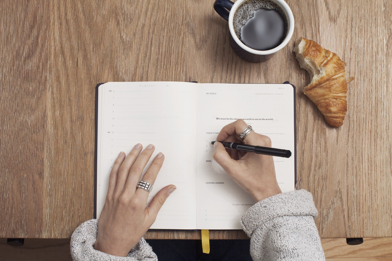 A woman writing in a notebook. Making a list of necessities is important when trying to find the right caregiver