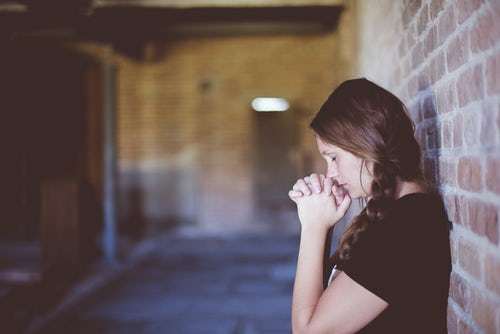 A young woman caregiver outside praying because she is under stress