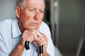 Senior man blanking staring into the distance while resting his head on his cane.