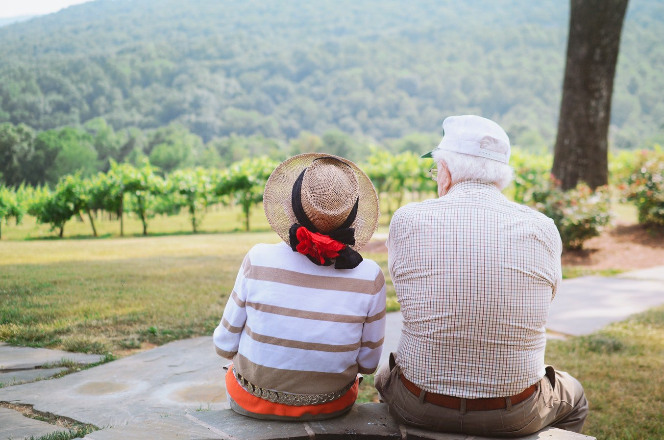 Two social seniors sitting together and looking at the outdoor scenery together.