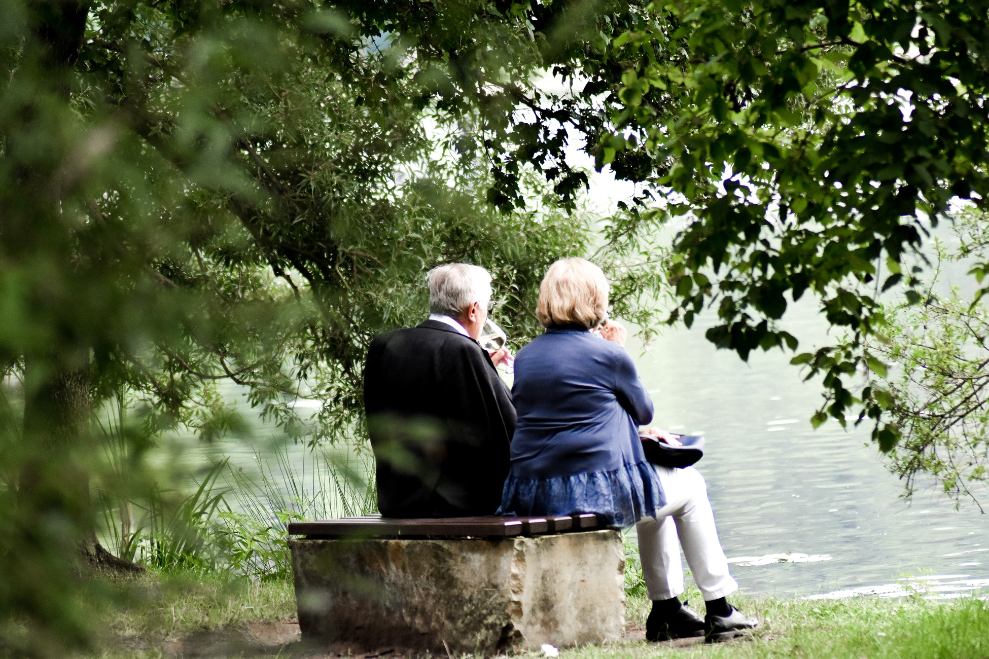 An elderly woman and her husband enjoying wine outdoors before they move to a memory care facility.