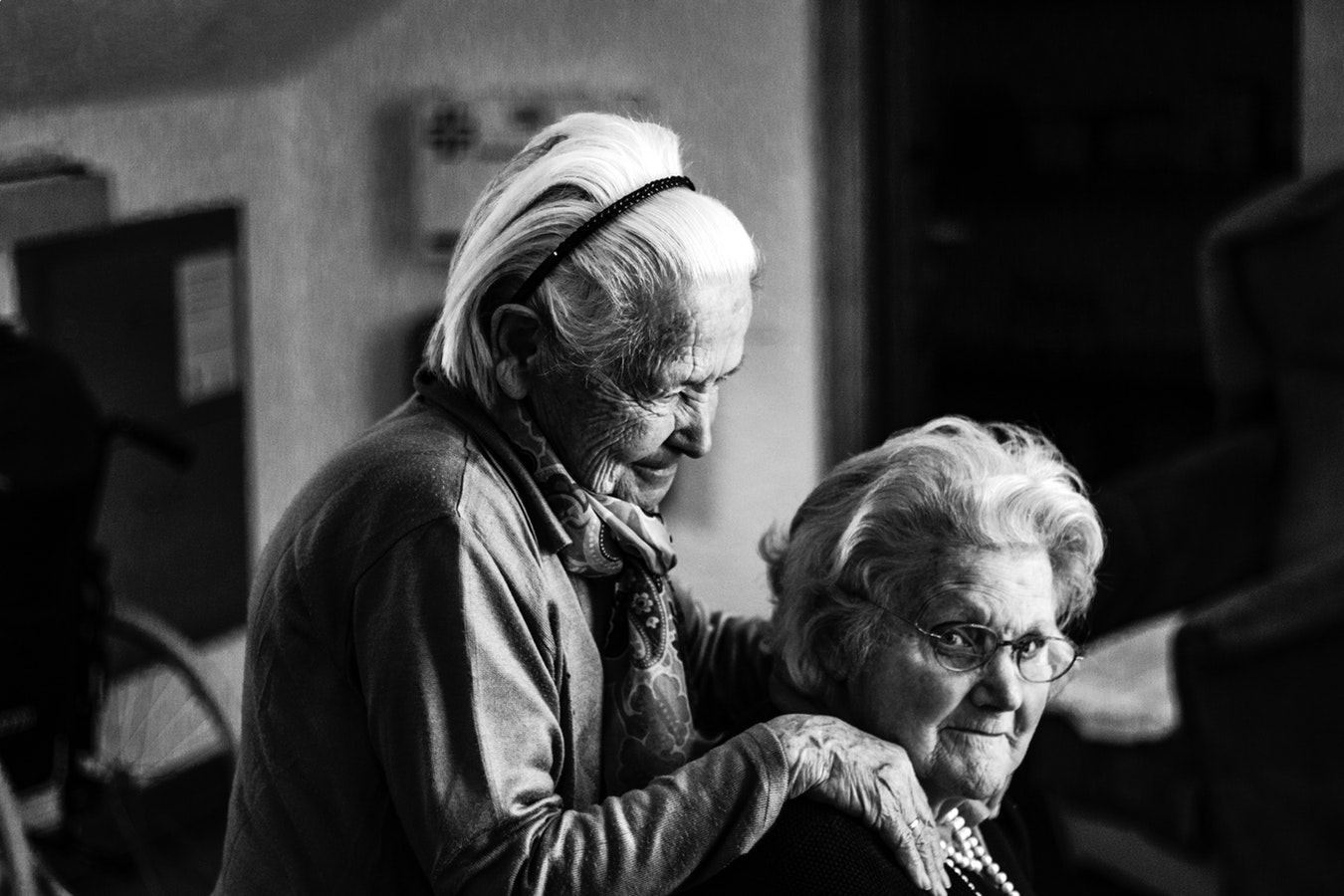 An elderly woman helping to comfort and create a safe enviorment for her friend with alzheimers
