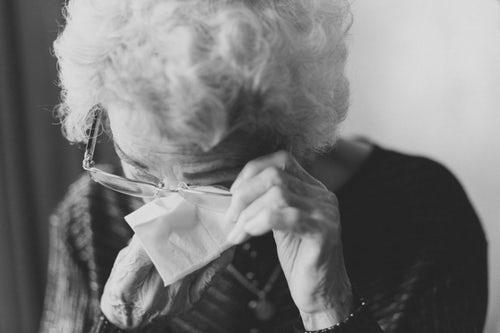 An elderly woman in distress wiping her eye
