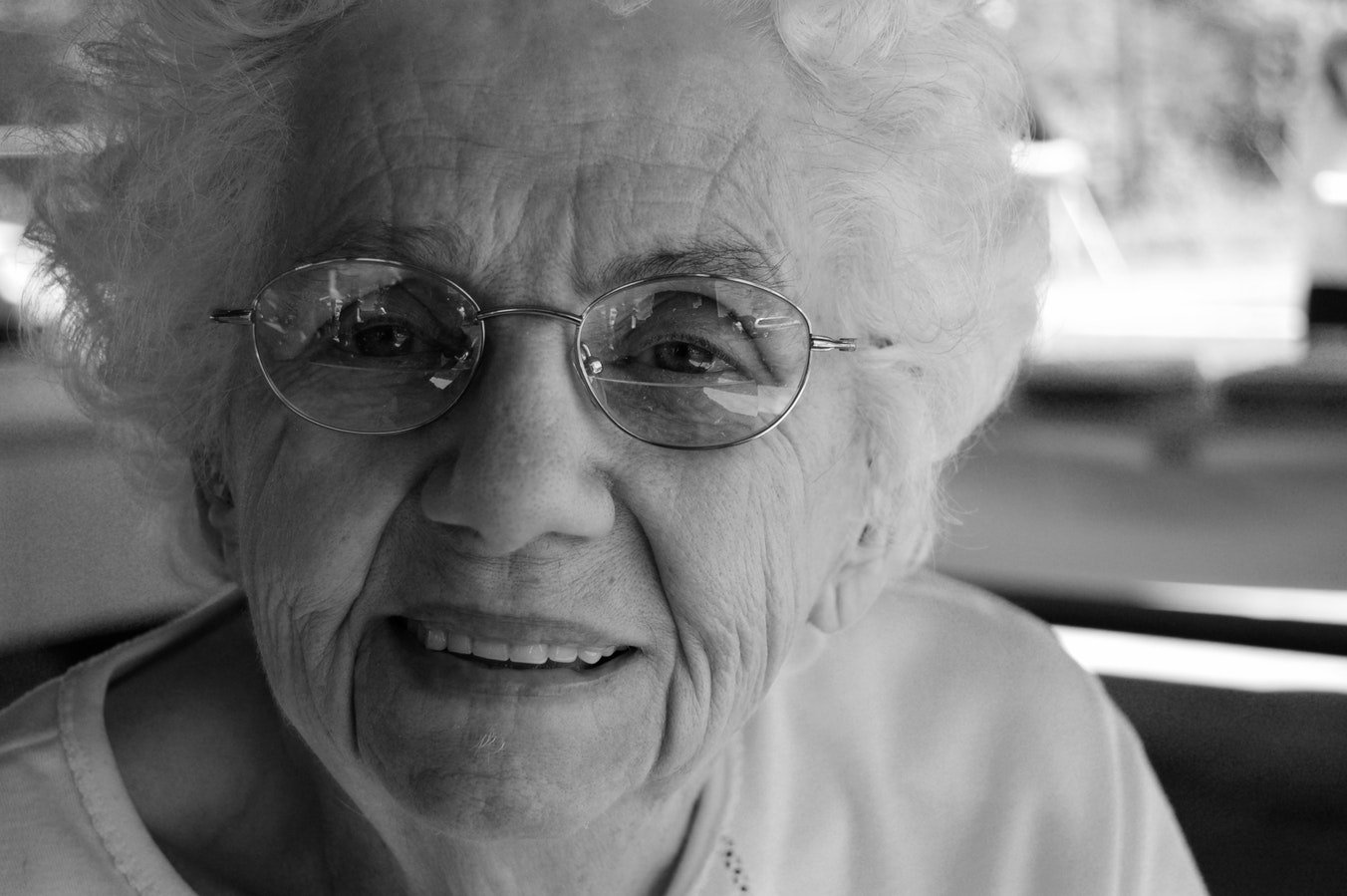 An elderly woman smiling. She is smiling because she practiced dental health for seniors.