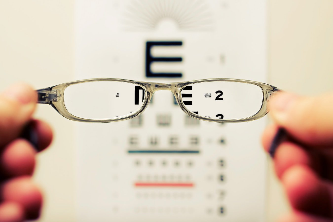 An individual holding glasses above an eye exam to see if they need cataract surgery