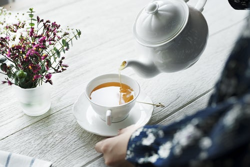 An individual pouring a hot cup of tea