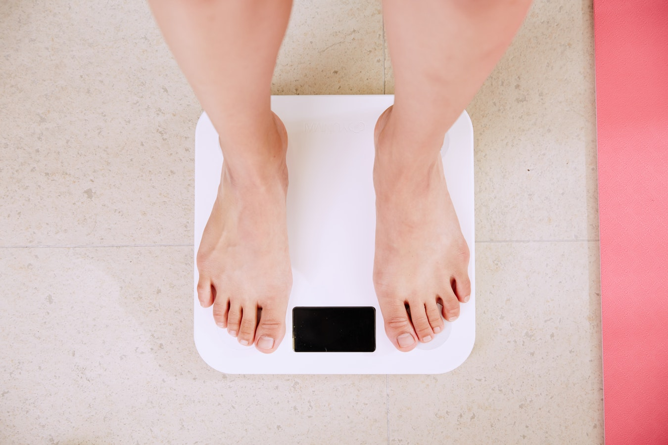 An individual stepping on a scale to keep track of their weight