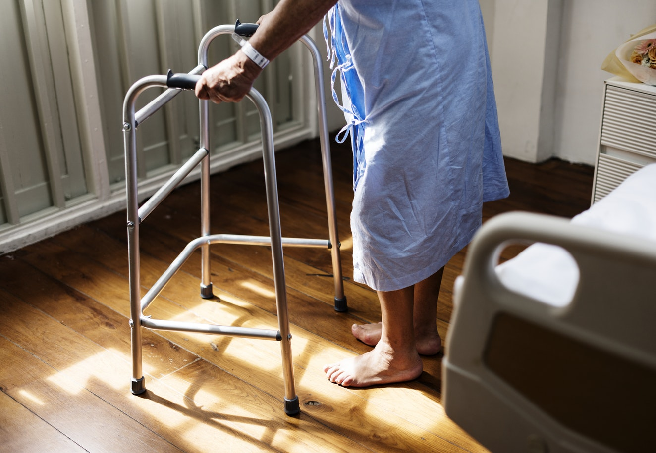 An individual using a walker to get out of their hospital bed