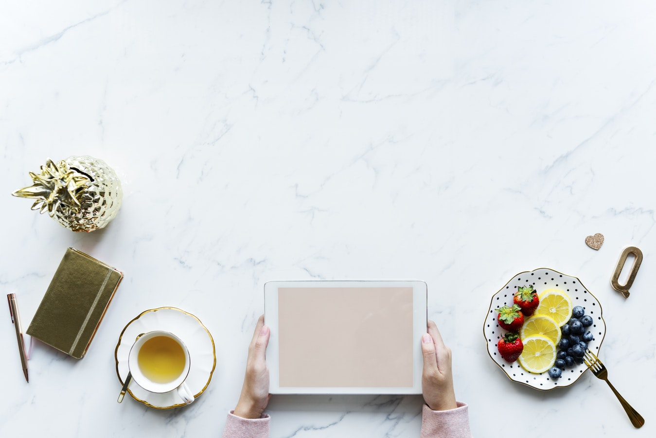 An individual using an Ipad on a table next to fruit and a cup of tea