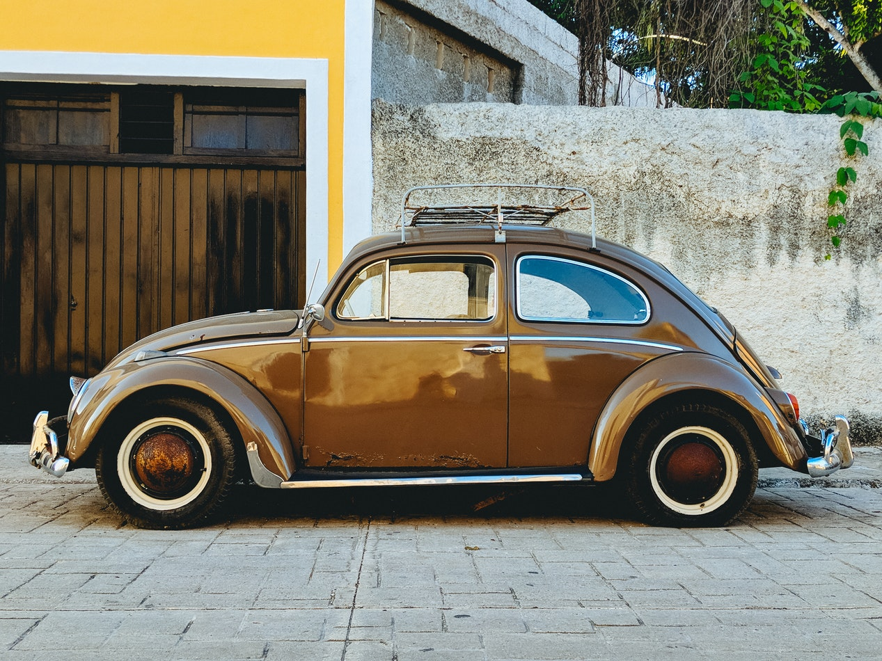 An older VW Beetle parked outside a building