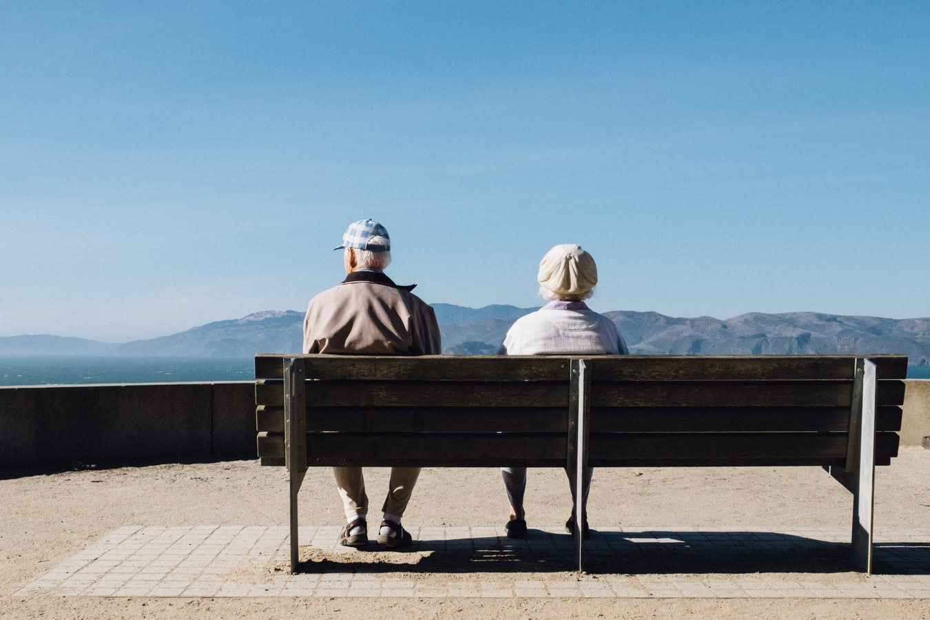 An older couple sitting on a bench and over looking the mountains. The wife is enjoying time with her husband who has Alzheimer's