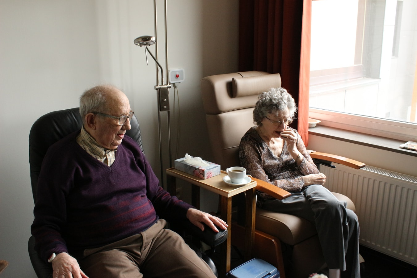 An older couple sitting together inside because she has pneumonia