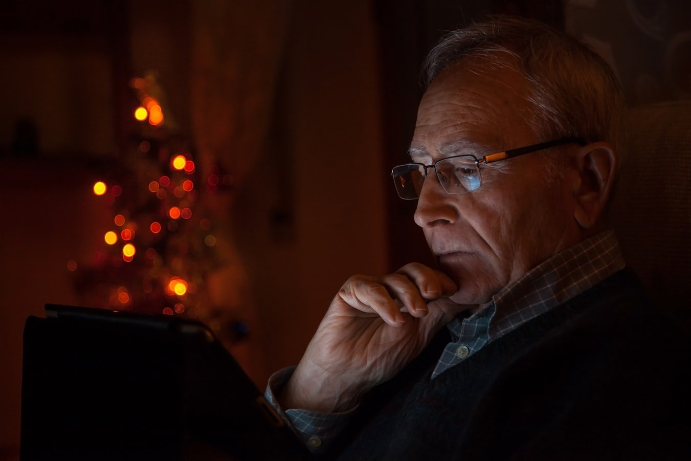 An older man reading on his ipad. A new study is showing that dementia patients moods are boosted after being given access to tablets