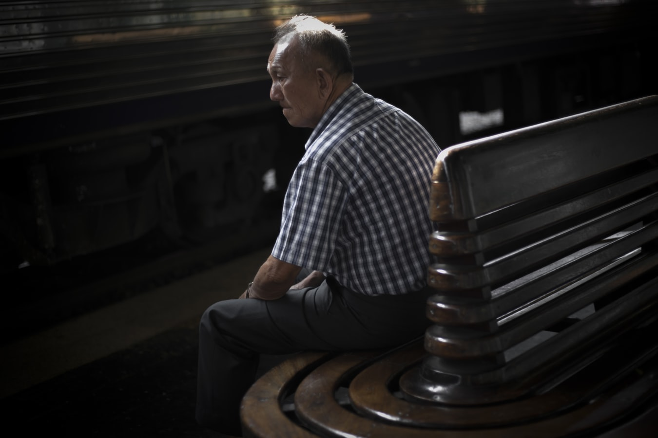 An older man sitting on a bench. PTSD in seniors is becoming more common