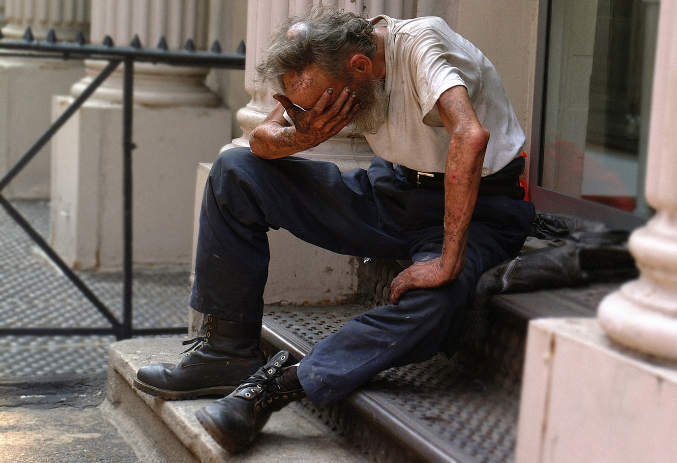 An older man sitting on the stairs and holding his head in his hand because he is suffering from depression
